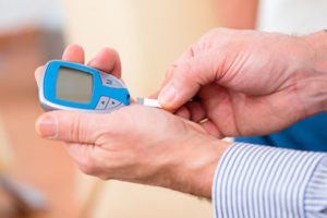 Senior with diabetes using blood glucose analyser